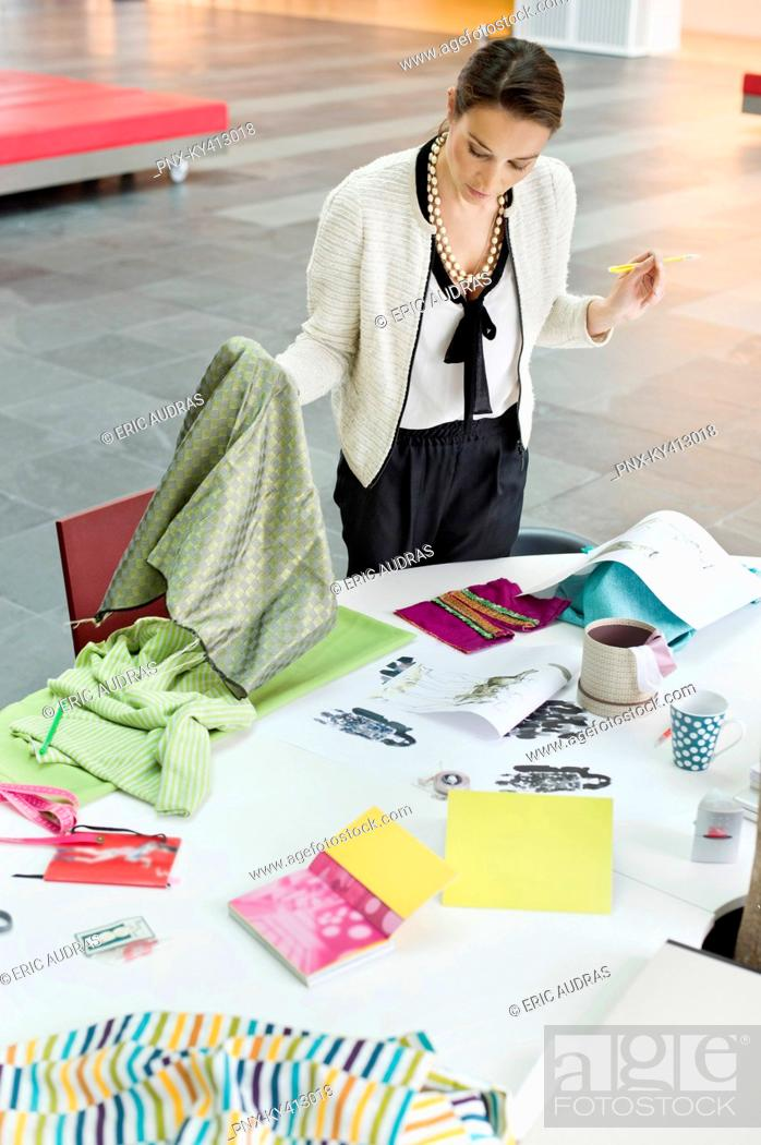 Stock Photo: Female fashion designer working in an office.