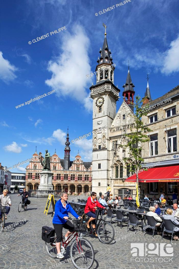 52ae01b969622 Stock Photo - Belfry and elderly tourists cycling past outdoor café on the town  square in Aalst / Alost, East Flanders, Belgium