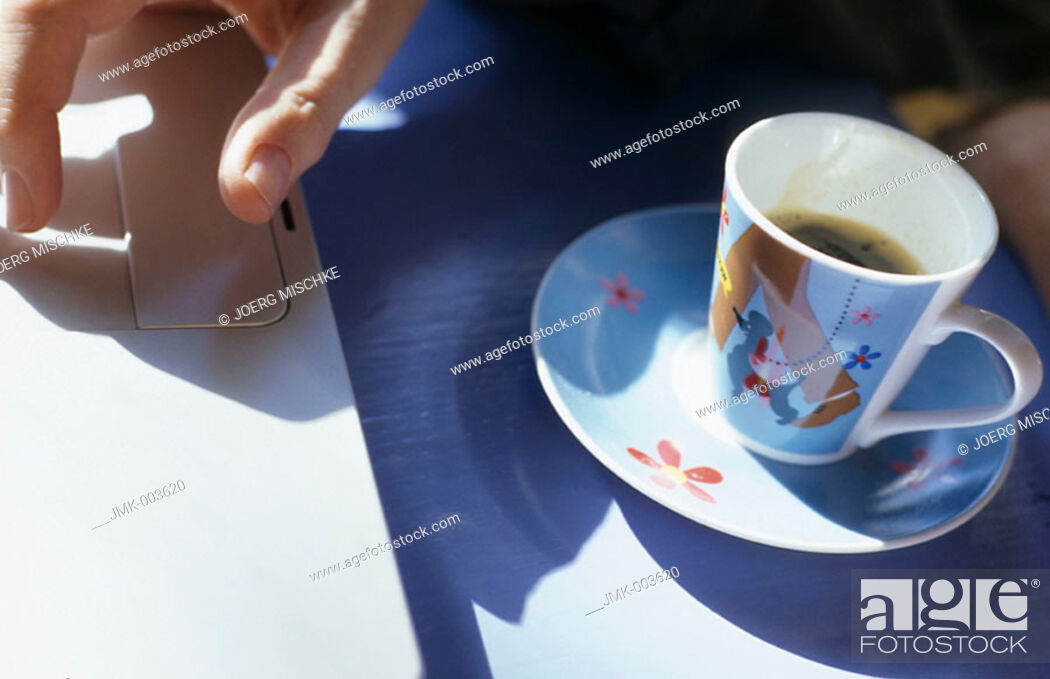 Stock Photo: The hand of someone working at a computer and an espresso cup.