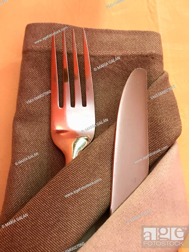 Stock Photo: Fork and knife in napkin.
