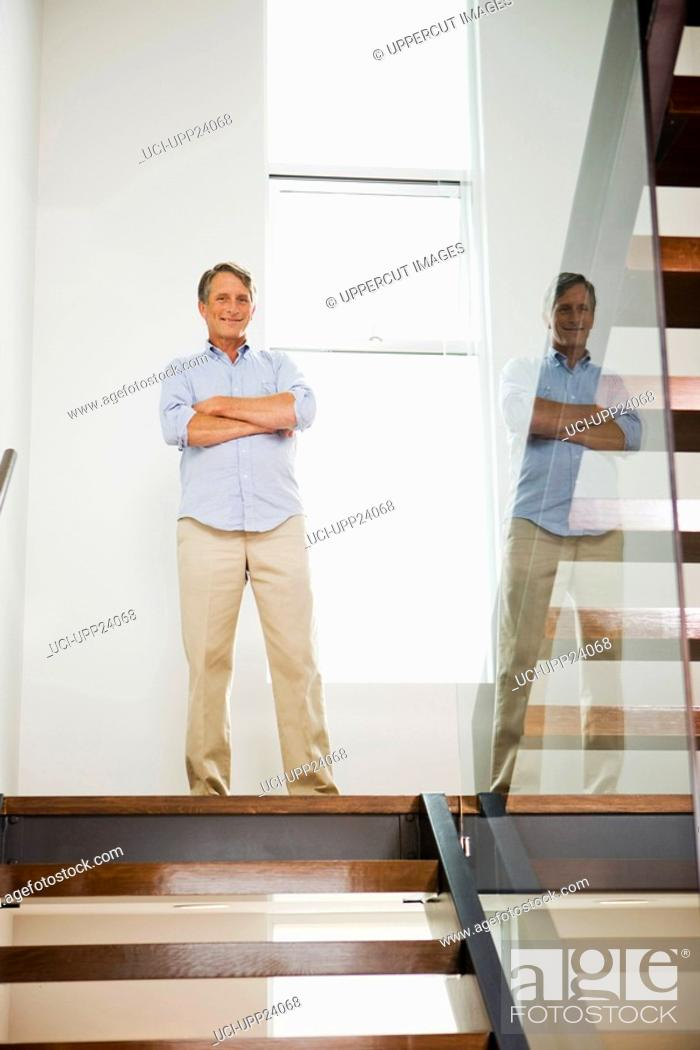 Stock Photo: Portrait of man standing on staircase landing.