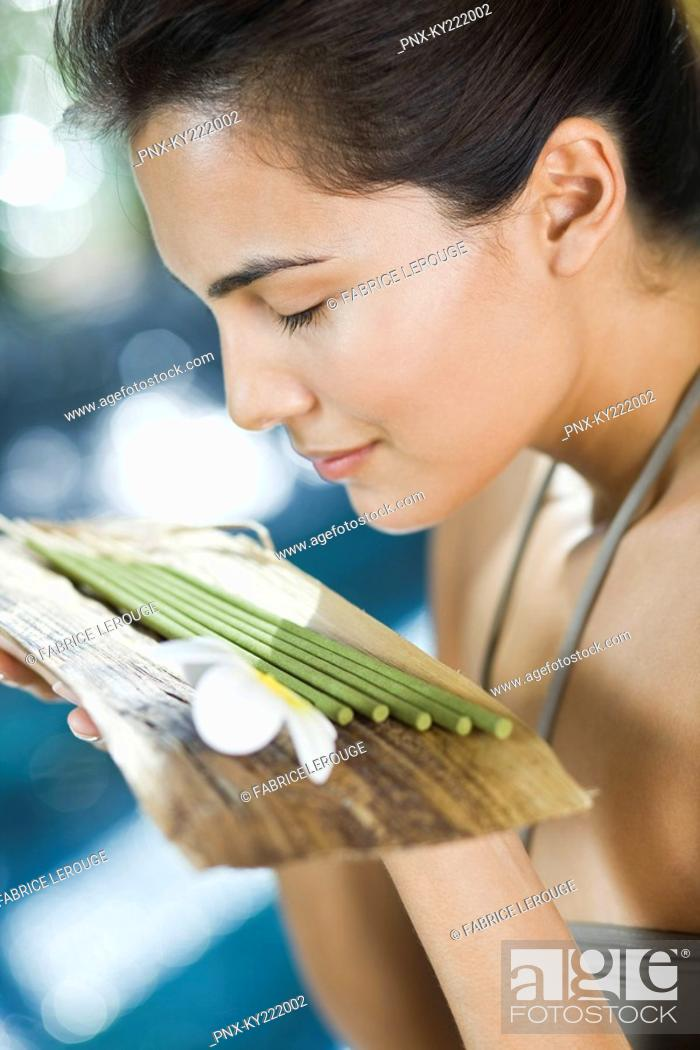 Stock Photo: Woman smelling incenses.