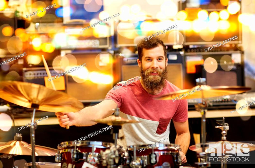 Imagen: male musician playing cymbals at music store.