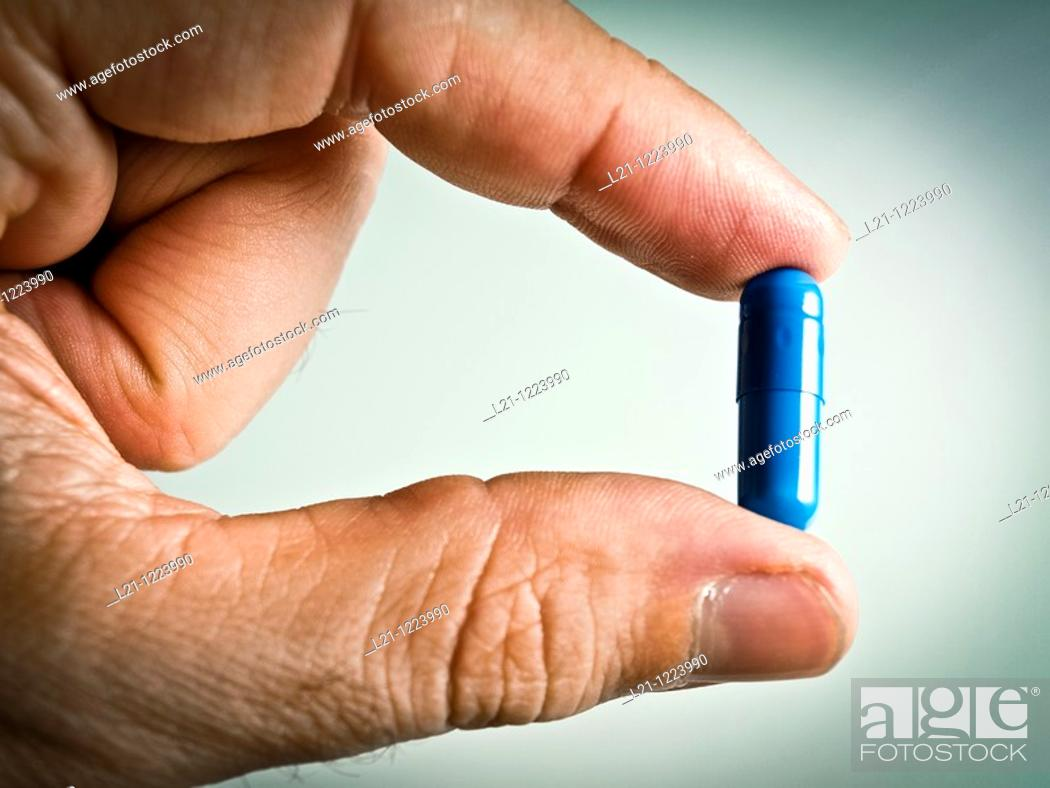 Stock Photo: Blue pill between two fingers.