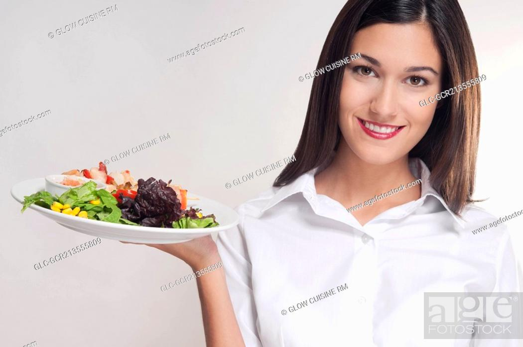 Stock Photo: Portrait of a young woman holding a platter of shish kebabs.