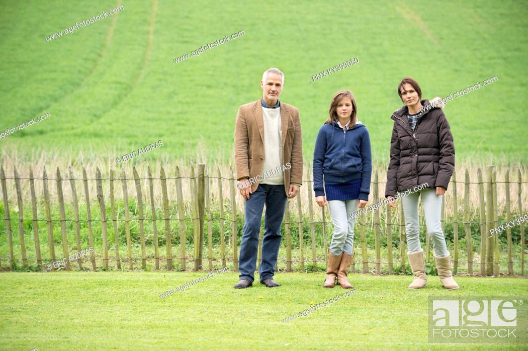 Stock Photo: Portrait of a happy family standing in a field.