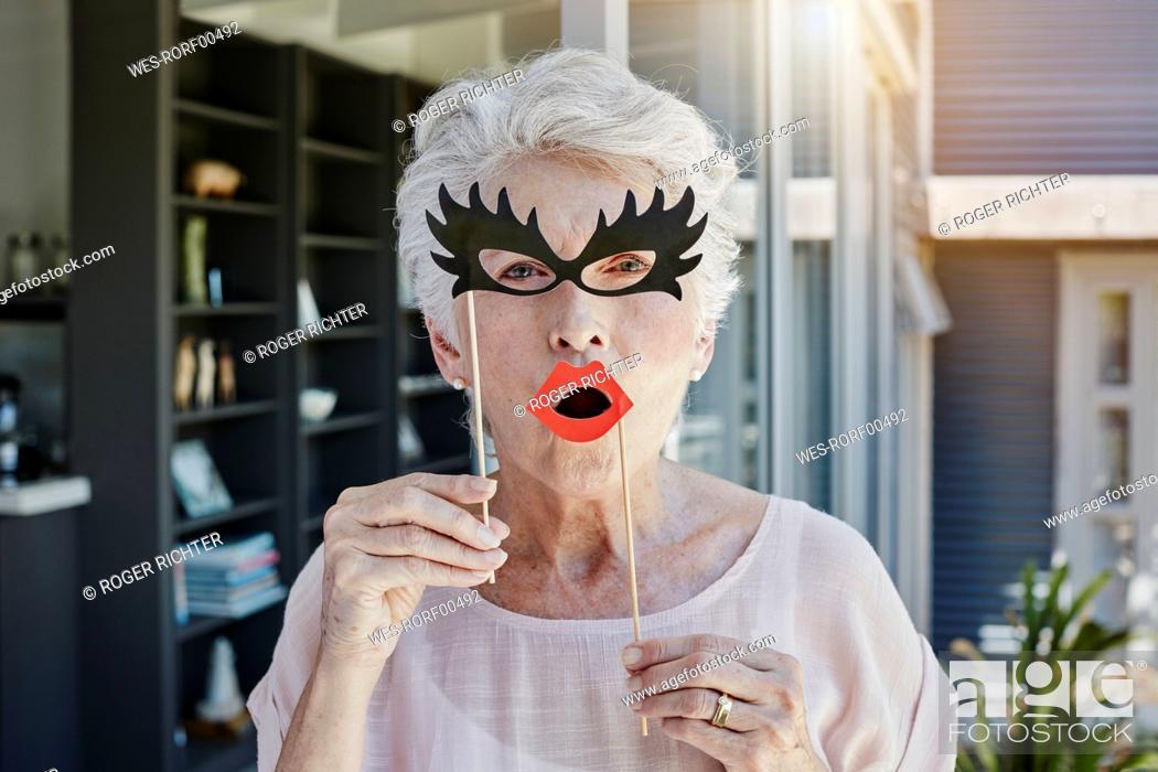 Stock Photo: Senior woman hiding behind paper masks.