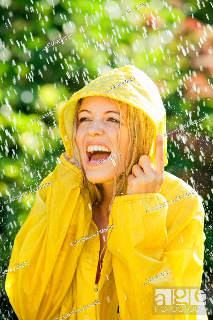 Stock Photo: Young woman wearing a raincoat enjoying the slight rain shower during a warm summers day.