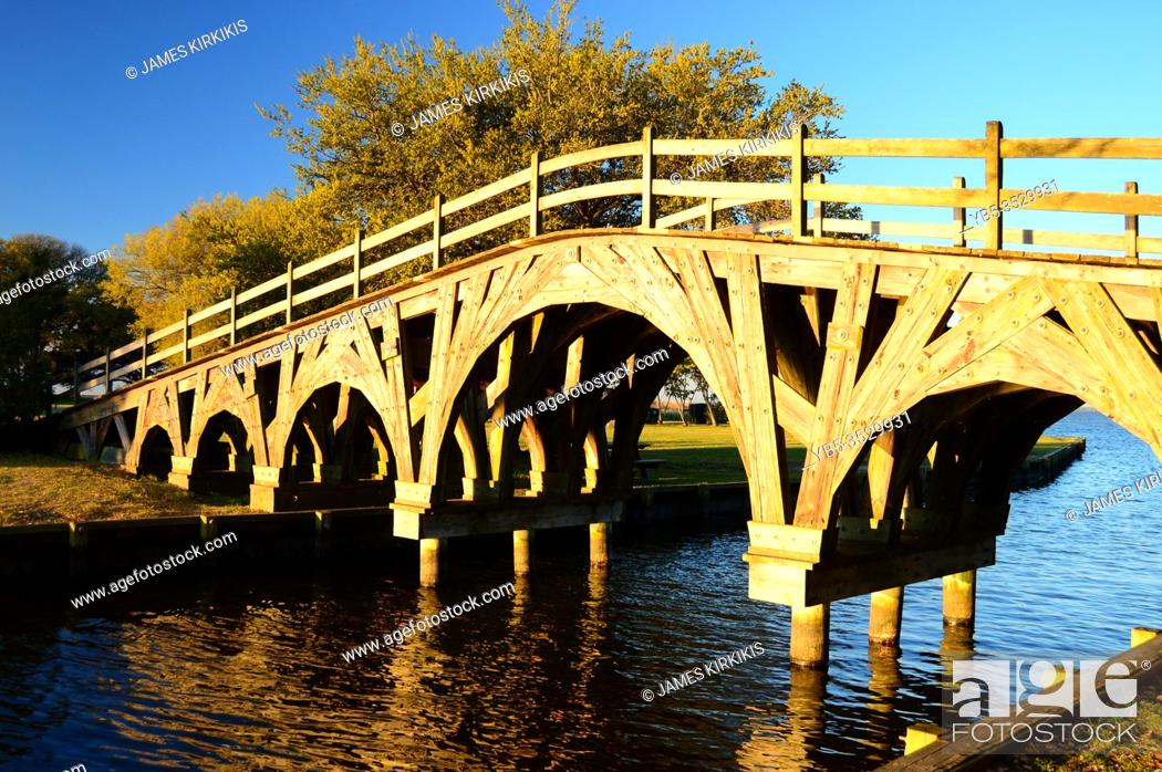 Stock Photo: A beautiful wooden pedestrian bridge crosses a small creek in a park in the Outer Banks of North Carolina.