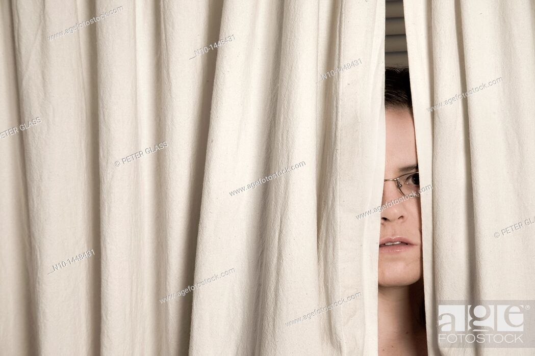 Stock Photo: Young woman, wearing glasses, peeking out from behind two curtains.