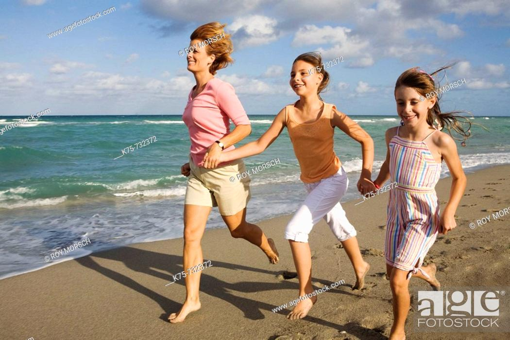 Stock Photo: mom running with her daughter and friend at bach.