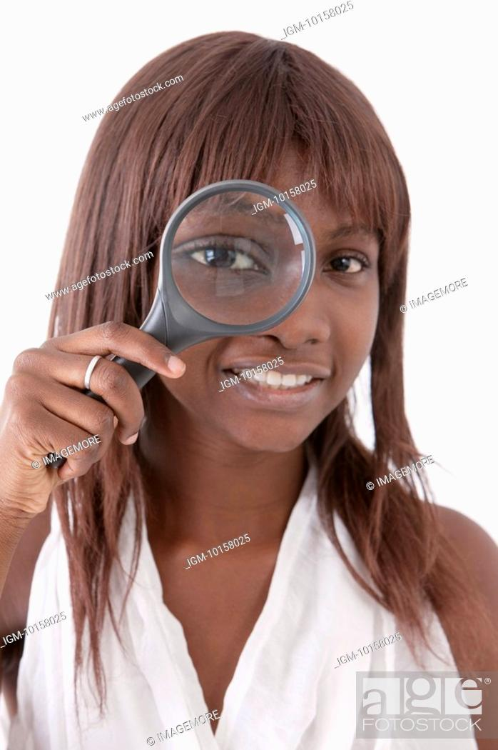 Stock Photo: Young woman putting magnifying glass on one eye and smiling.