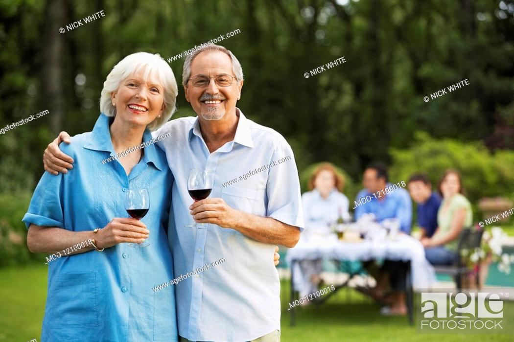 Stock Photo: Middle-aged couple in back yard with glasses of wine portrait.