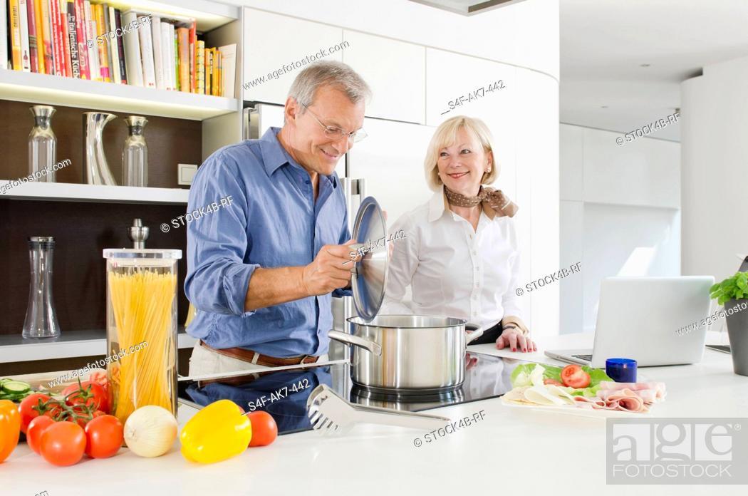 Stock Photo: Senior couple preparing healthy pasta meal in kitchen.