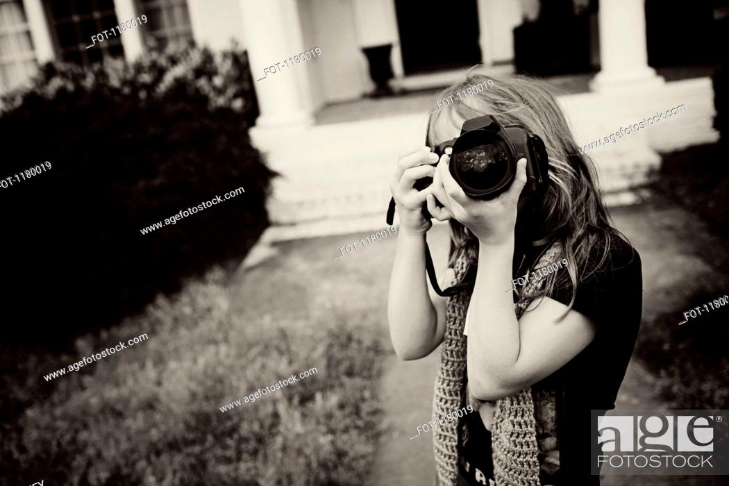 Stock Photo: A young girl using a camera.