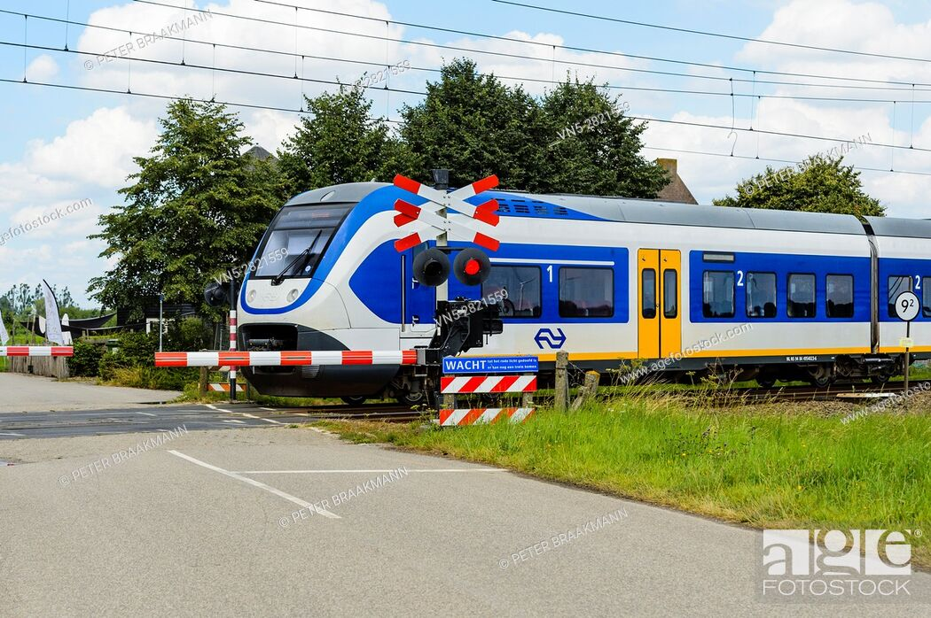 Stock Photo: HOEVEN, THE NETHERLANDS - AUGUST 1: Train moving at high speed on a level crossing on August 1, 2016 in The Netherlands.