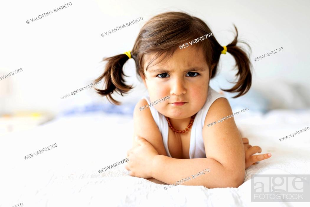 Stock Photo: Portrait of little girl lying on bed at home pulling funny face.
