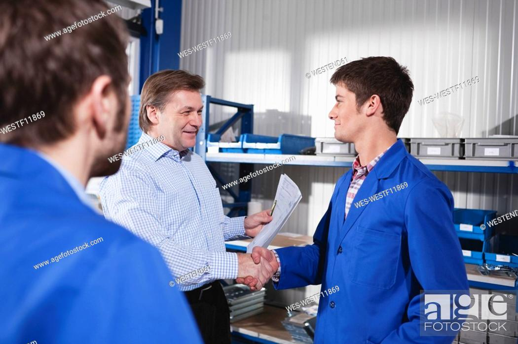 Stock Photo: Germany, Neukirch, Apprentice and instructor shaking hands, side view.