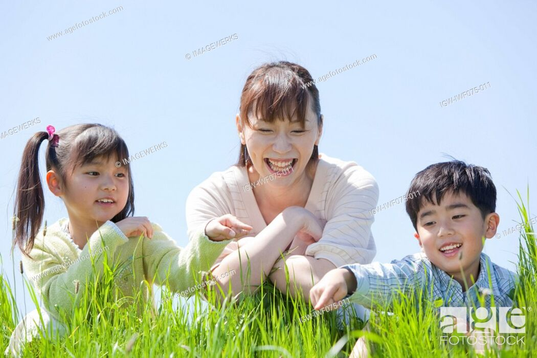 Stock Photo: Japan, Tokyo Prefecture, Mother and children in meadow looking at grass, smiling.