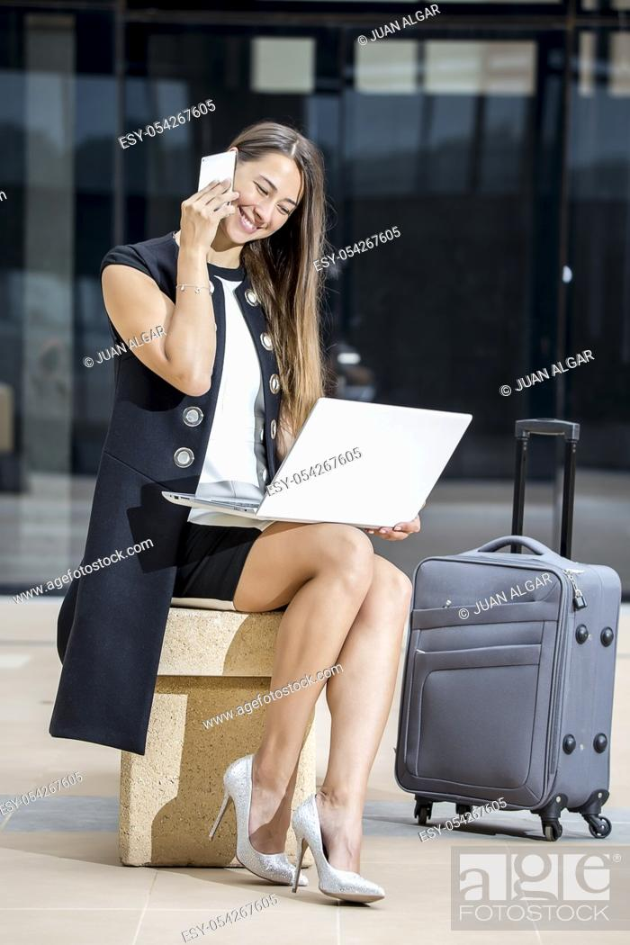 Stock Photo: Young elegant businesswoman using laptop and talking smartphone while sitting at street with suitcase.