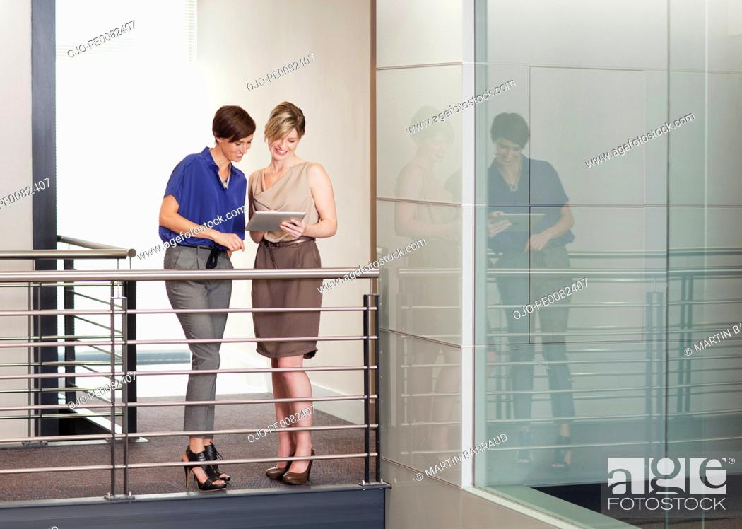 Stock Photo: Businesswomen with digital tablet on elevated walkway in office.