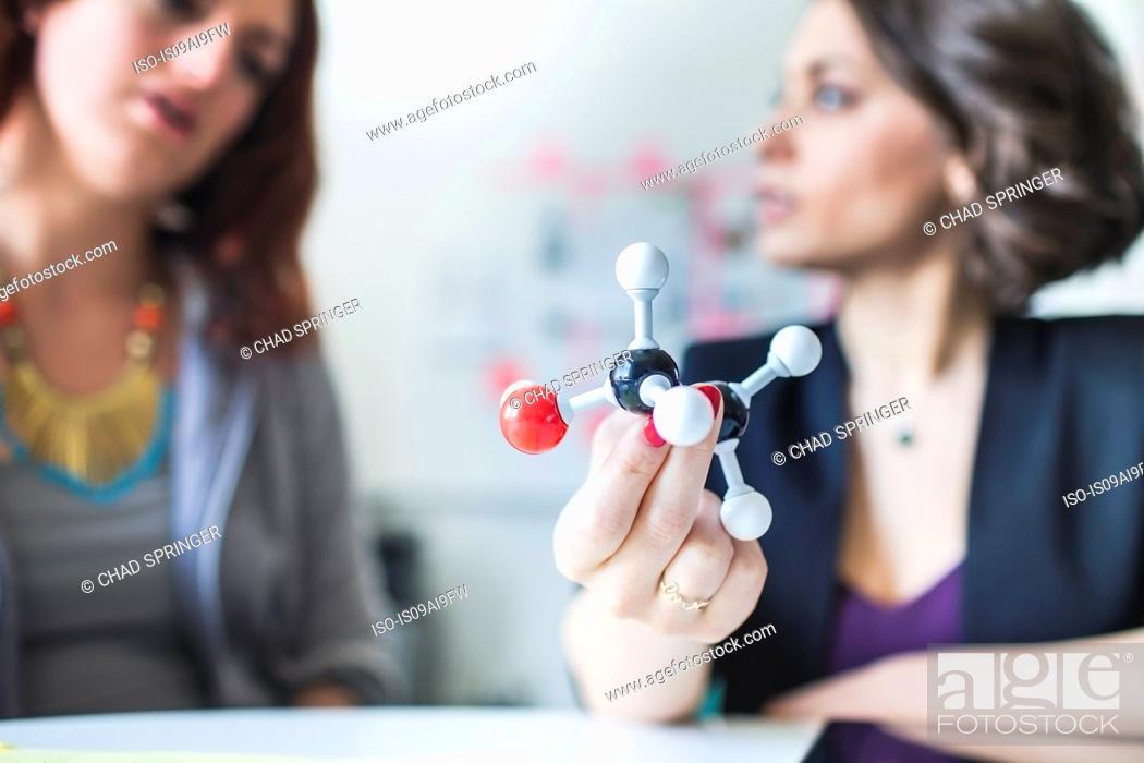 Stock Photo: Young women discussing molecular model of Ethanol molecule.