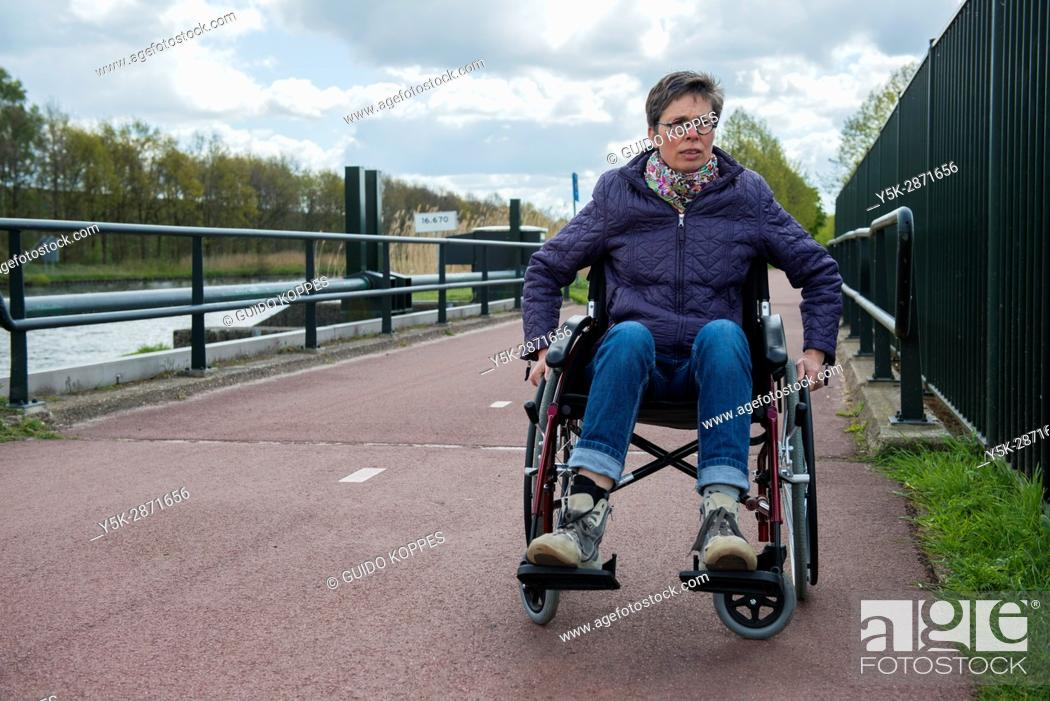 Photo de stock: Tilburg, Netherlands. Female multiple sclerosis patient dealing with her condition by on and off using a wheelchair to get along.