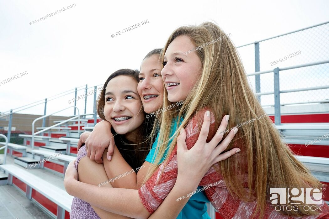 Stock Photo: Teenage girls hugging on bleachers.
