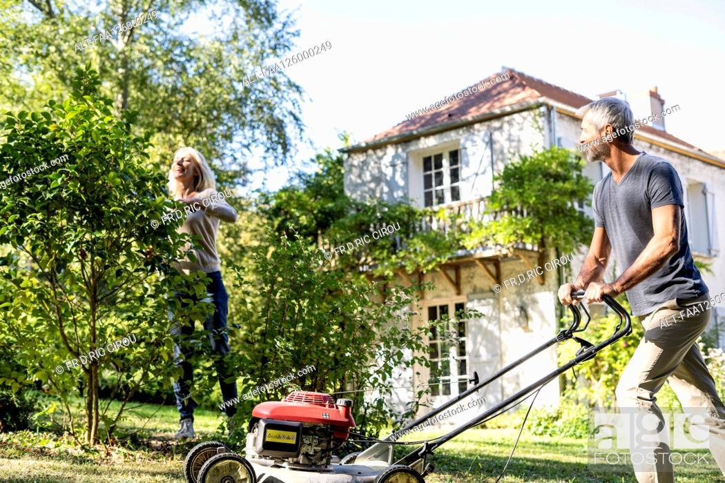 Photo de stock: Mature couple gardening together in backyard.
