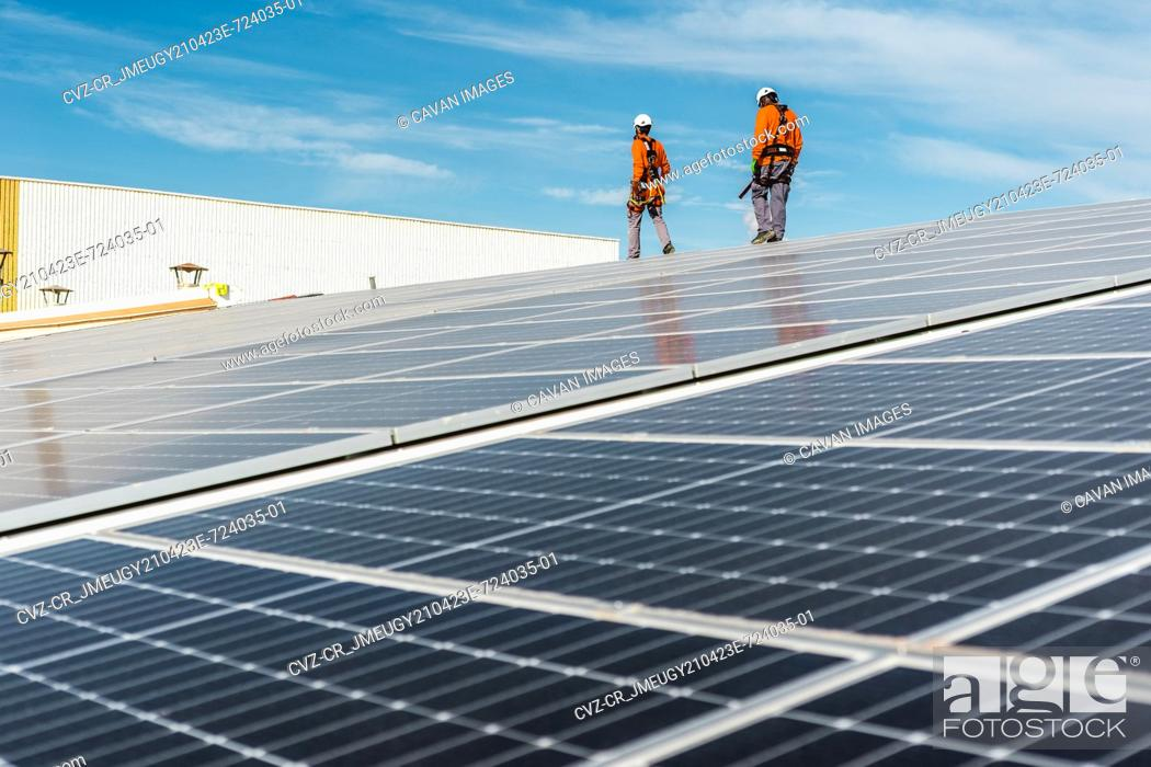 Photo de stock: Installation with multiple solar panels with technicians walking backw.