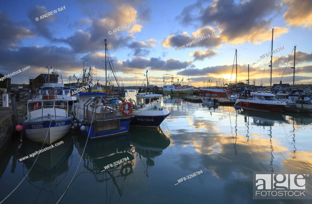 Stock Photo: Boats in Padstow Harbour on the North Coast of Cornwall, capture shortly after sunrise on a still morning in January.