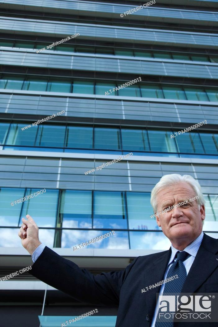 Stock Photo: Executive pointing at office building, portrait.
