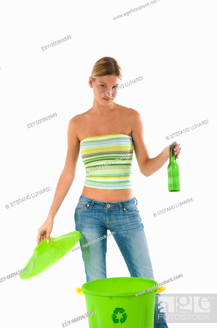 Stock Photo: Young woman putting a bottle in recycle bin.