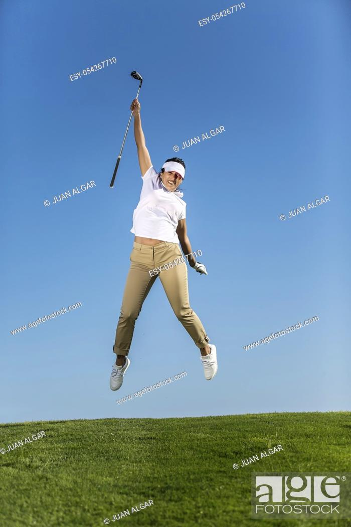 Stock Photo: Beautiful excited woman holding golf driver and jumping high above green meadow of field against blue sky.