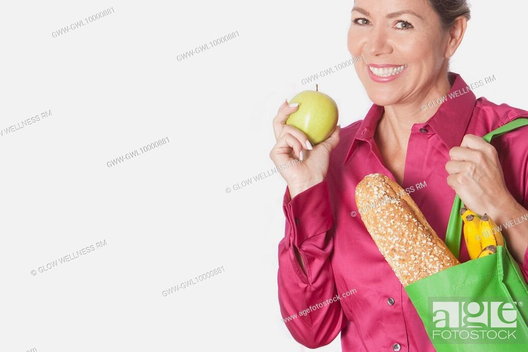 Imagen: Woman holding a shopping bag of groceries with fruits.