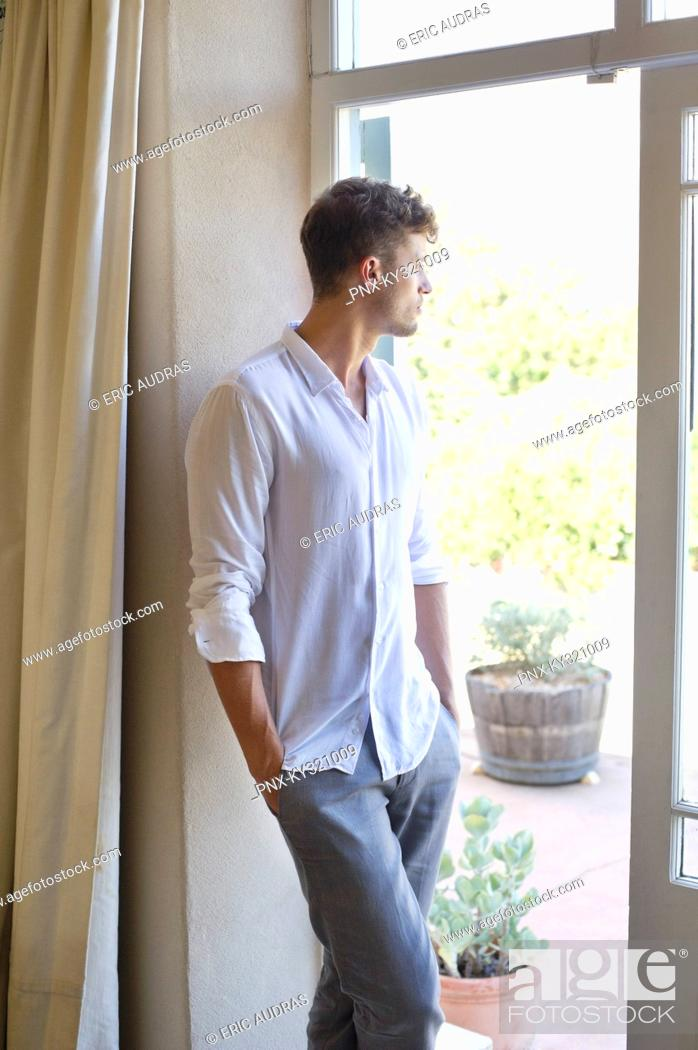 Stock Photo: Side profile of a man standing at door with hands in pocket.