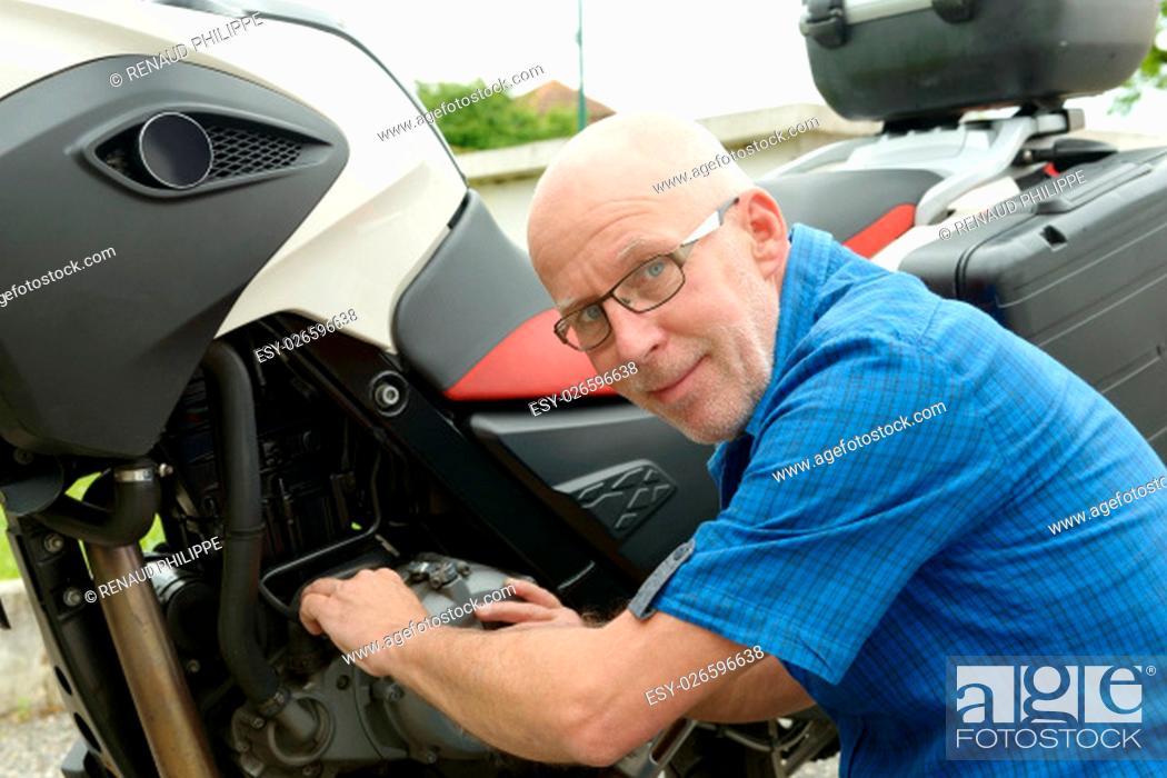 Stock Photo: a senior man repairing motorbike outdoor.