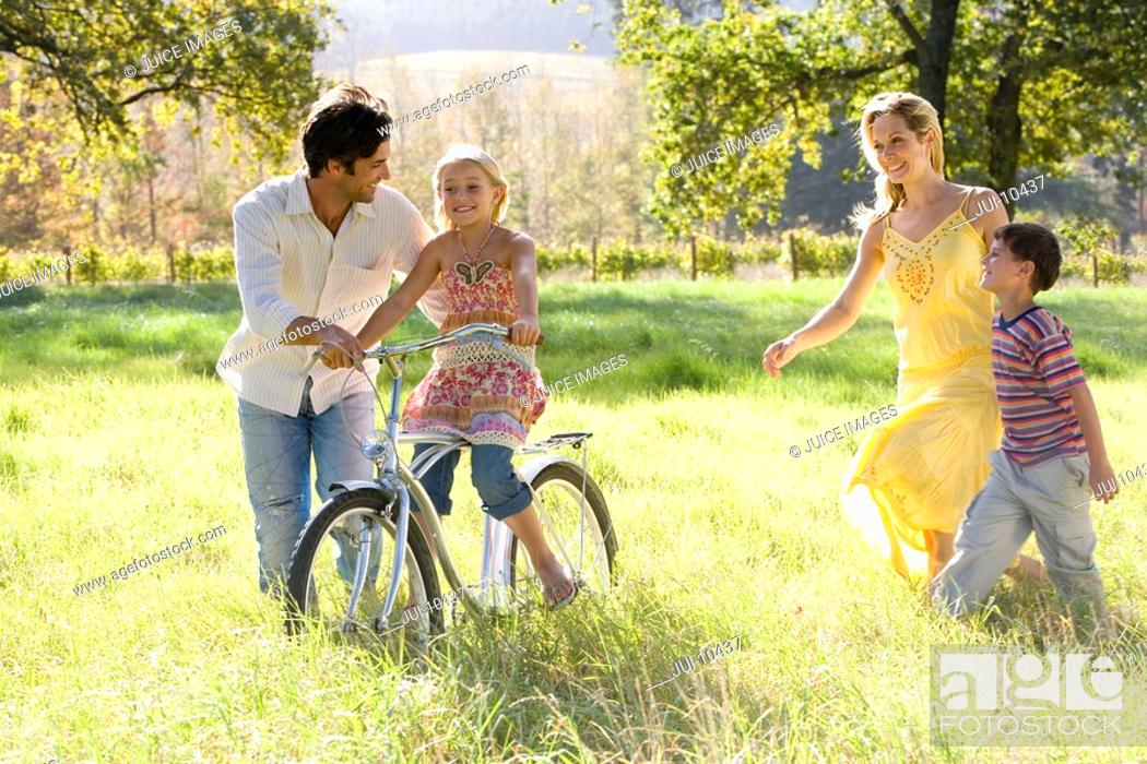 Stock Photo: Family of four in field, father helping daughter 5-7 on bicycle, smiling.
