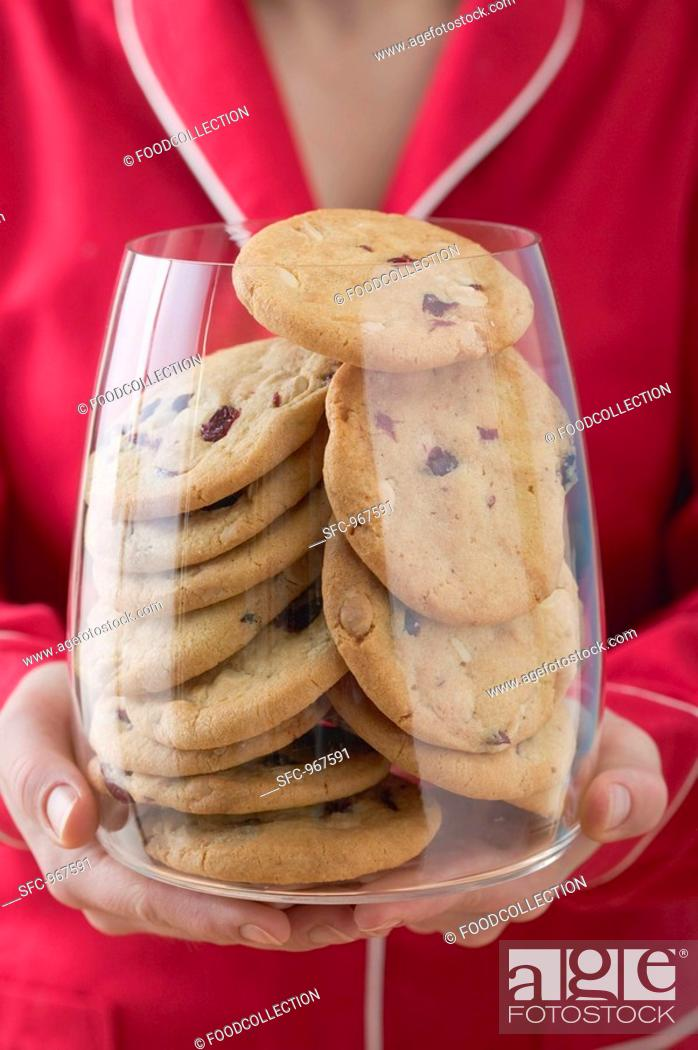 Stock Photo: Woman holding glass full of cranberry cookies.