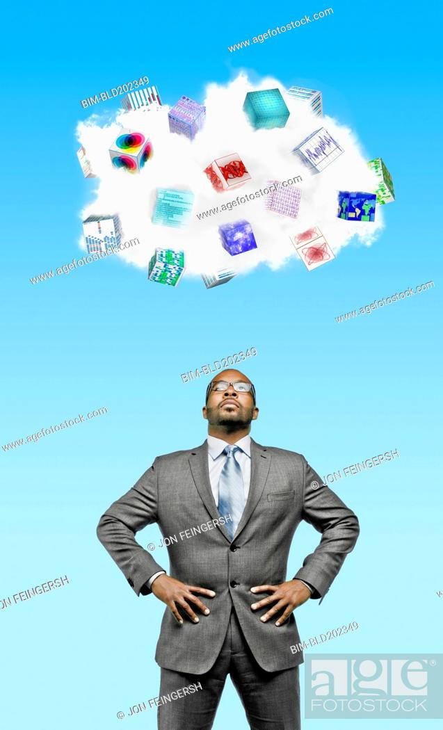 Stock Photo: African American businessman looking at cloud containing cubes with pictures.