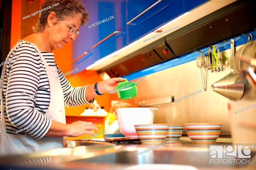 Stock Photo: Senior woman in kitchen, measuring ingredients into mixing bowl.