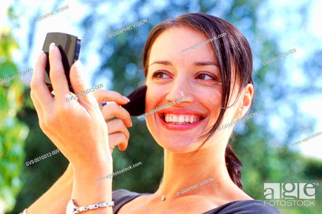 Stock Photo: Young woman applying makeup.