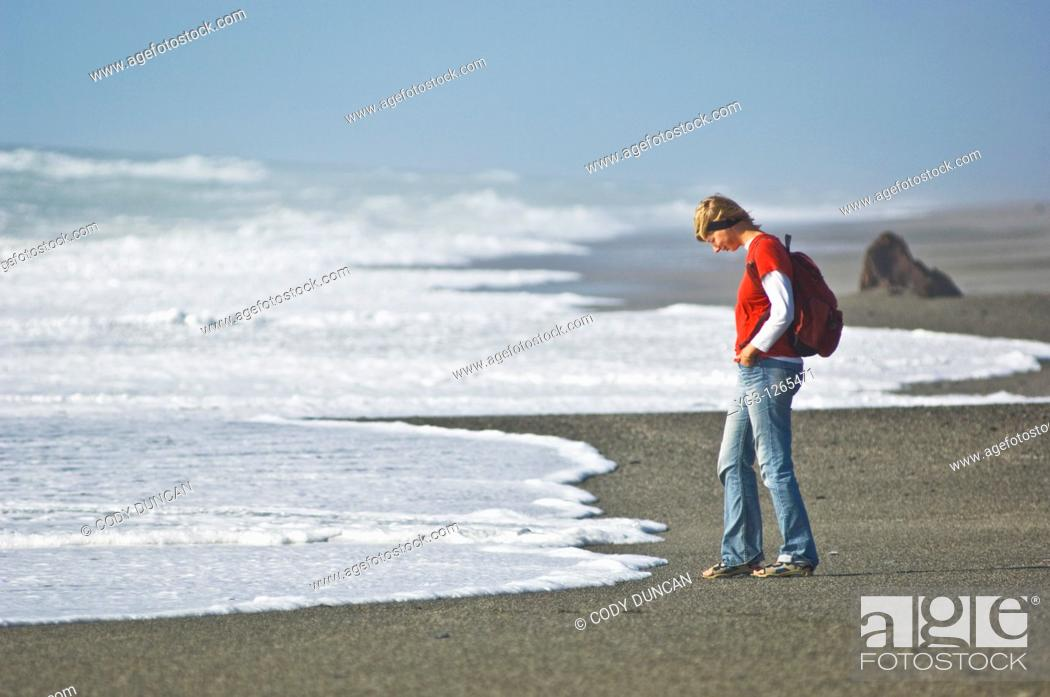 Stock Photo: woman watching incoming waves on empty beach.