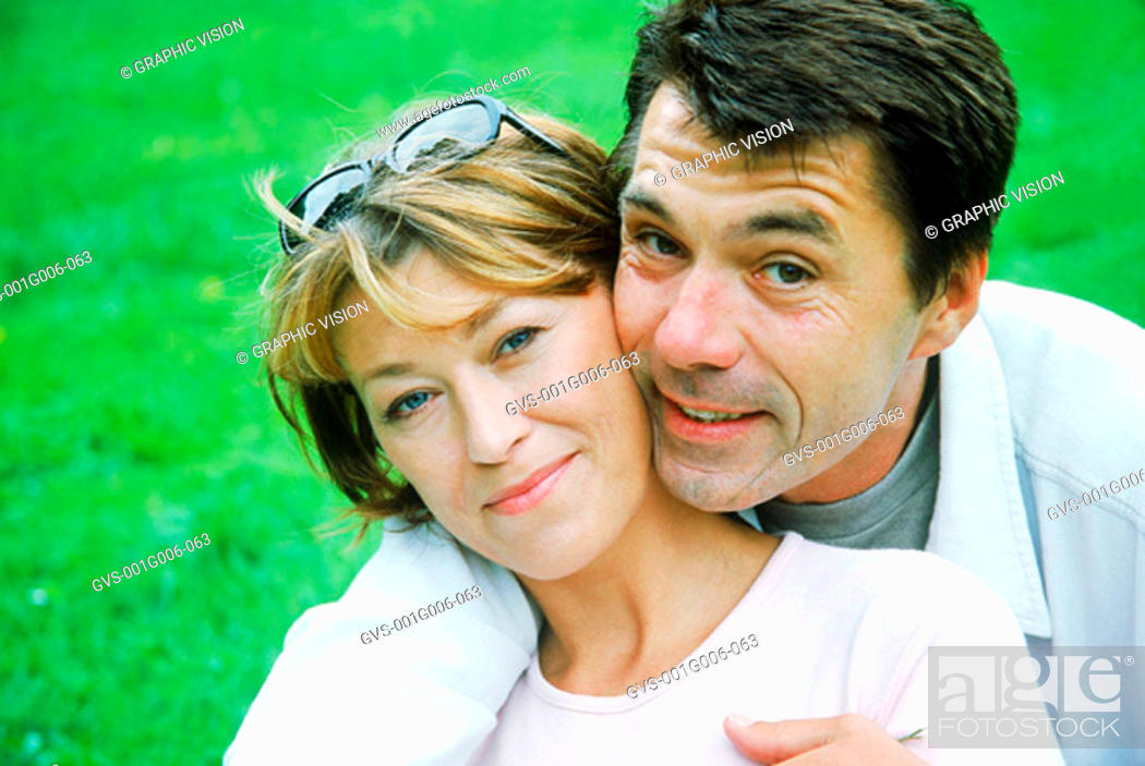 Stock Photo: Portrait of a couple holding each other on a lawn.
