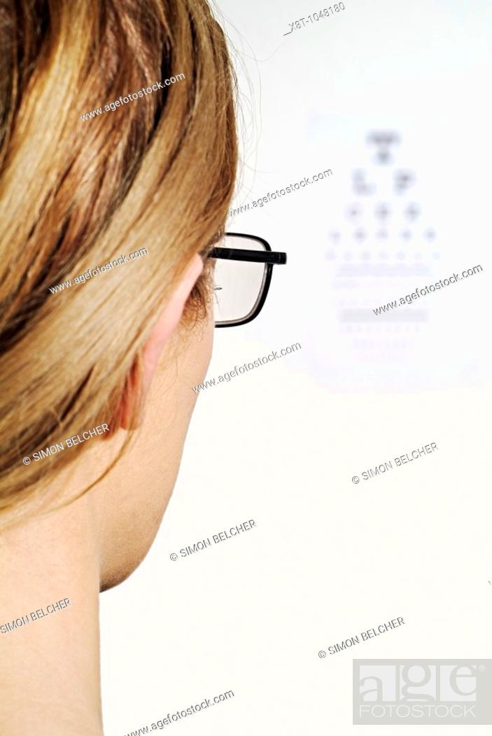 Woman Having Her Eye Sight With Spectacles Checked By Reading A