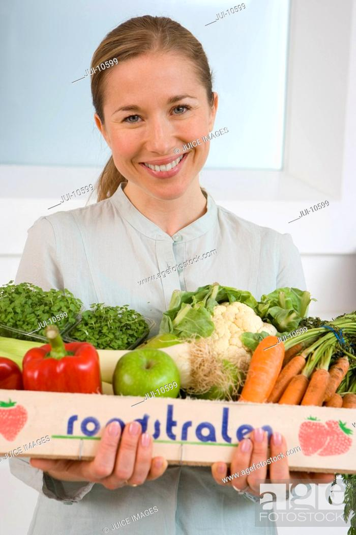 Stock Photo: Woman with box of vegetables, smiling, portrait, close-up.