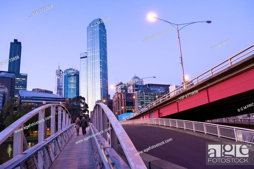 Stock Photo: couple walking on pedestrian bridge and Kings Bridge, with Melbourne city skyline.