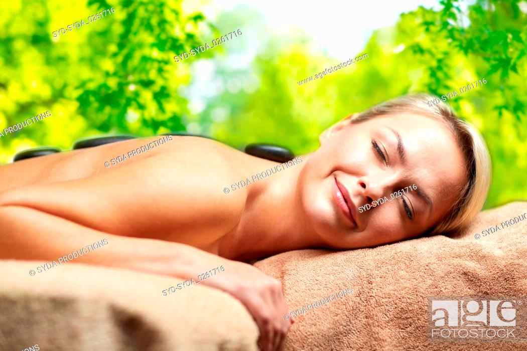 Stock Photo: close up of woman having hot stone massage in spa.