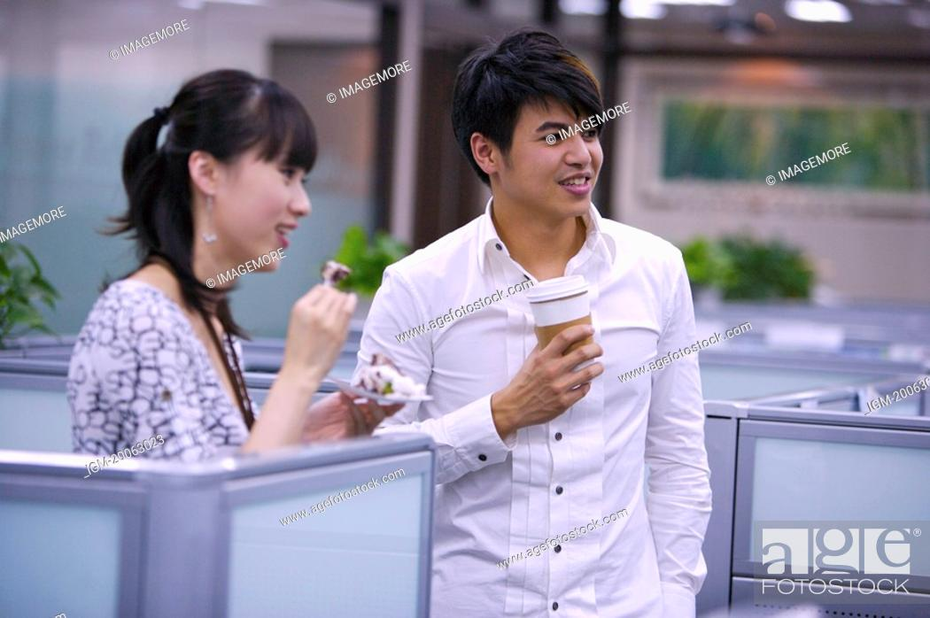 Stock Photo: Young woman and man eating or drinking at coffee break and smiling.