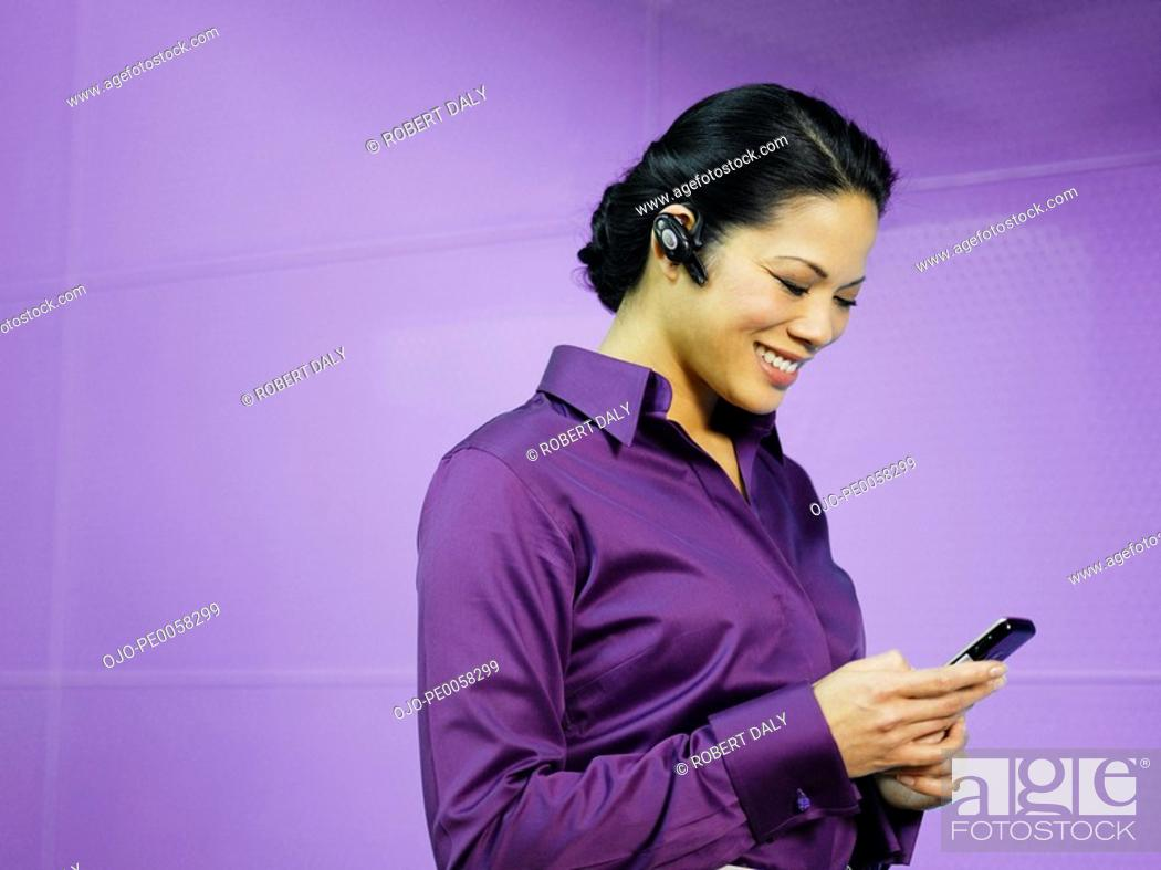 Stock Photo: Businesswoman with mobile phone and earpiece in purple office.